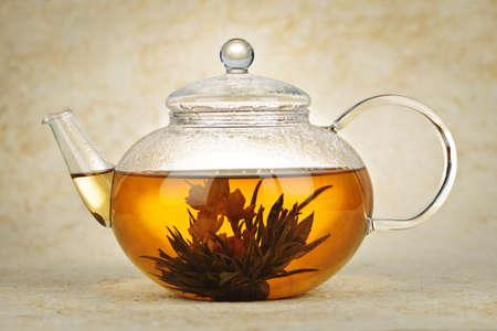 ガラスのティーポットの緑茶に咲く花