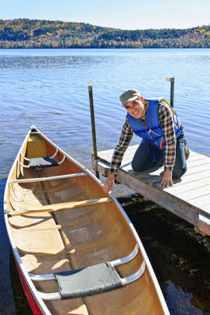 Man holding canoe at dock on Lake of Two Rivers, Ontario, Canada