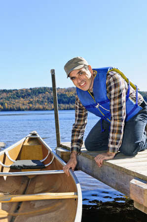 lifejacket: Man holding canoe at dock on Lake of Two Rivers, Ontario, Canada