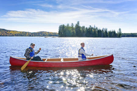 piragua: Familia de piragüismo en el soleado lago de dos ríos, Ontario, Canadá