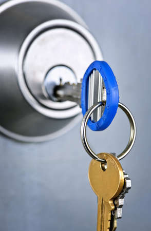 slot met sleuteltje: Keys ingevoegd in deurslot close up