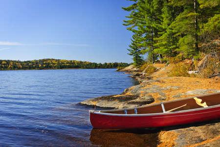 piragua: Canoa rojo en rocosa orilla de lago de dos r�os, Ontario, Canad� Foto de archivo