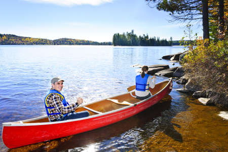 boating: Family in red canoe near rocky shore of Lake of Two Rivers, Ontario, Canada