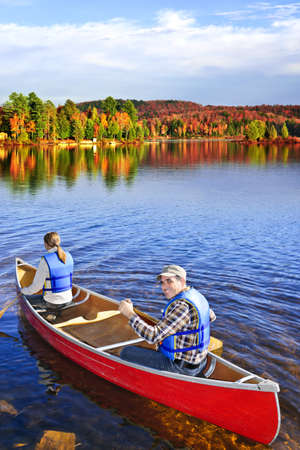 People canoeing on scenic lake in fall, Algonquin park, Canada photo