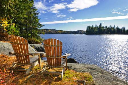 2 つの川、オンタリオ州、カナダの湖の岸でアディロンダックの椅子 写真素材