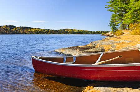 piragua: Canoa roja en la costa rocosa del Lago de los Dos Ríos, Ontario, Canadá Foto de archivo