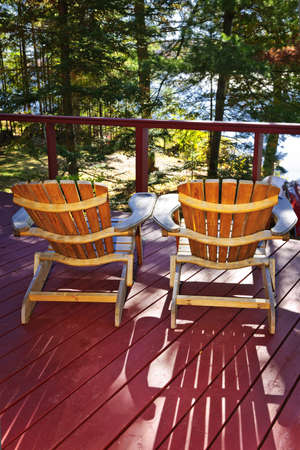 casa de campo: Deck de madera en la cabaña del bosque con sillas Adirondack
