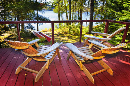 Wooden deck of cottage with Adirondack chairs at lake photo