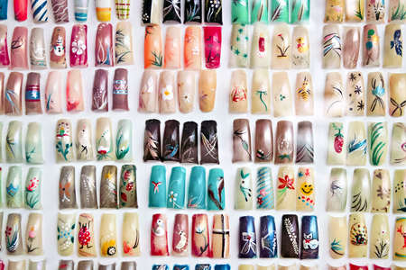 Artificial acrylic nails painted in various designs on display in nail salon