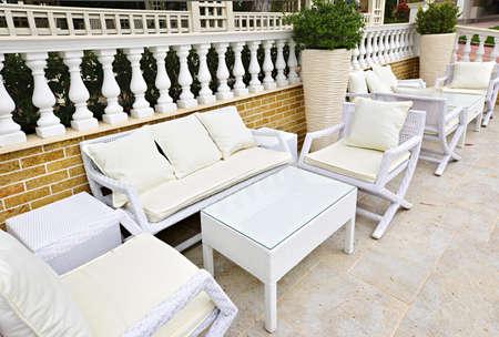 patio furniture: Mobilia del patio di vimini esterno in area pavimentata con pietra naturale