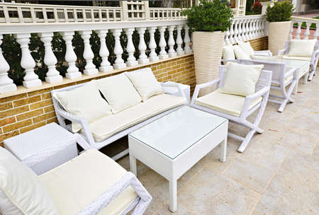 furnishings: Wicker patio furniture outdoor in area paved with natural stone