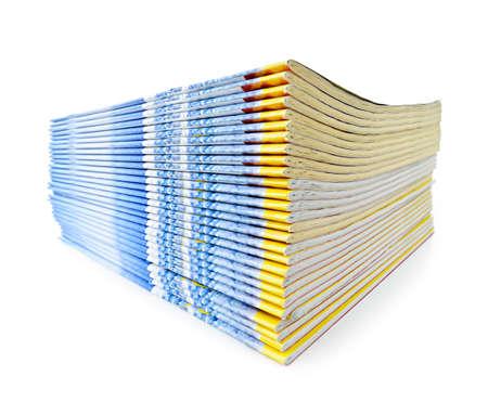 Veel tijdschriften gestapeld in een stapel op wit wordt geïsoleerd