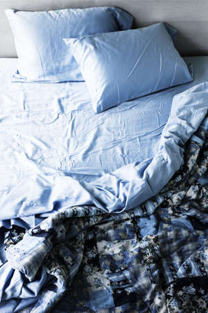 Unmade messy bed with wrinkled sheets from above photo