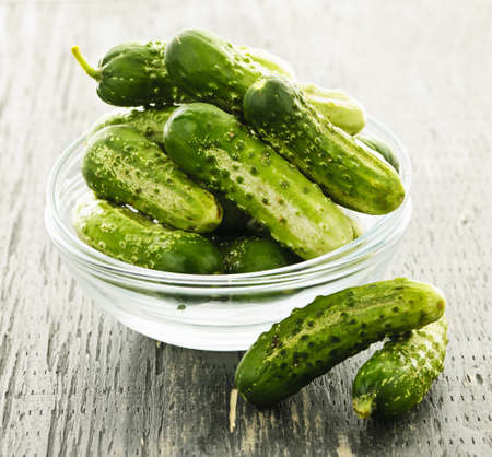 cucumbers: Fresh green pickling cucumbers in a glass bowl