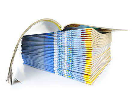 print media: Many magazines stacked in a pile with one open isolated on white Stock Photo