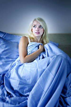 잠 못 이루는 밤 금발의 여자는 침대에서 밤에 무서워