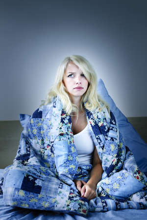 wrapped up: Sleepless blonde woman in bed with insomnia