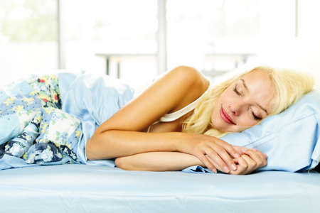 Young woman peacefully asleep in bed in the morning Stock Photo