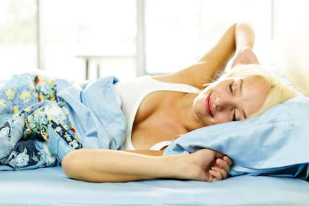 Woman waking up stretching in bed with morning sunshine photo
