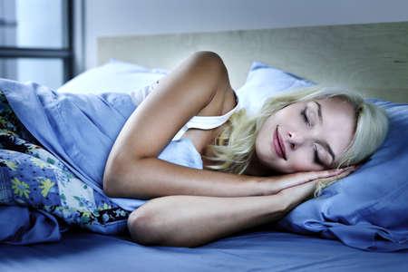 lit: Jeune femme dort paisiblement pendant la nuit dans le lit