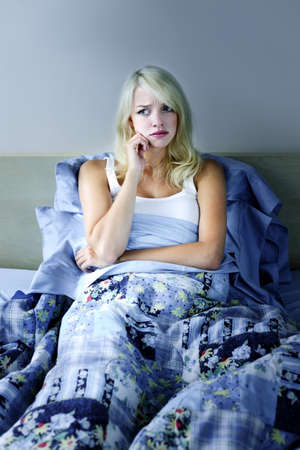 worrying: Sleepless blonde woman in bed with insomnia