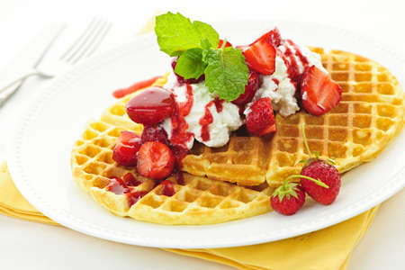 Plate of belgian waffles with fresh strawberries and whipped cream photo