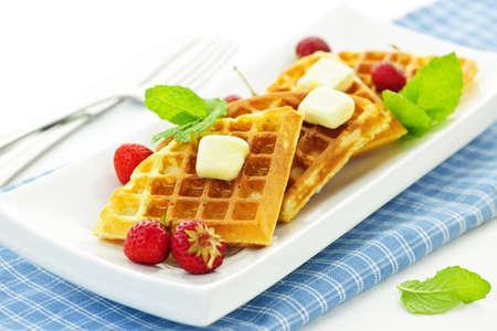 waffles: Plato de gofres belgas con fresas frescas y porciones de mantequilla