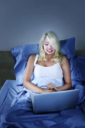 밤에 침대에서 랩톱 컴퓨터를 사용 무서 워 여자 스톡 콘텐츠