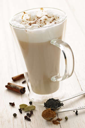 latte: Chai latte spiced tea beverage in glass mug with spices