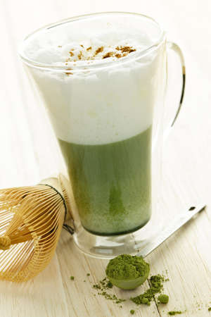 matcha: Matcha green tea latte beverage in glass mug with whisk