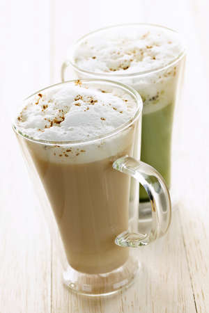 Two specialty tea latte beverages of chai and matcha teas photo