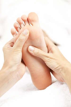 manos y pies: Hembra manos dando masaje a pie desnudo suave Foto de archivo