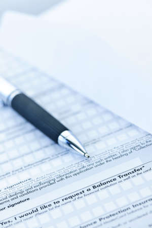 Blank credit application form with envelope and pen close up photo
