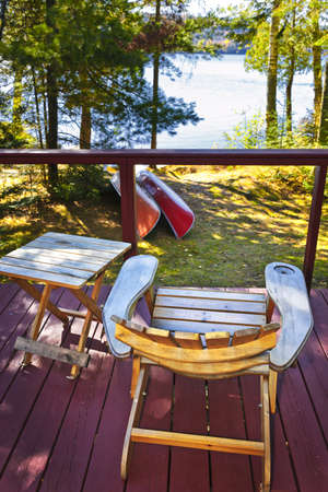 Wooden deck of cottage with lake view and Adirondack chair Stock Photo - 10637550