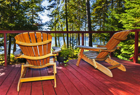 adirondack chair: Wooden deck at forest cottage with Adirondack chairs