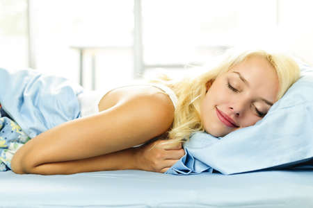 bedding: Young woman sleeping cozy in bed in the morning Stock Photo