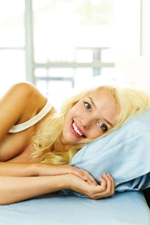 snug: Happy blonde woman laying in bed and smiling in the morning at home Stock Photo