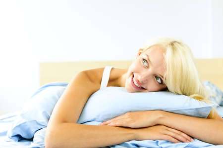 Happy blonde young woman laying in bed dreaming and smiling photo
