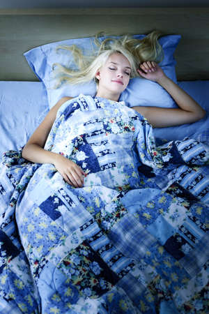 bedroom: Young woman sleeping peacefully at night in bed Stock Photo