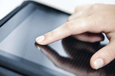Vrouwelijke hand aanraken van tablet-computer scherm met de vinger