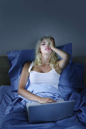 troubles: Worried young woman with laptop computer in bed at night Stock Photo
