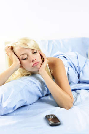 jilted: Lonely blonde woman waiting for phone call in bed at home