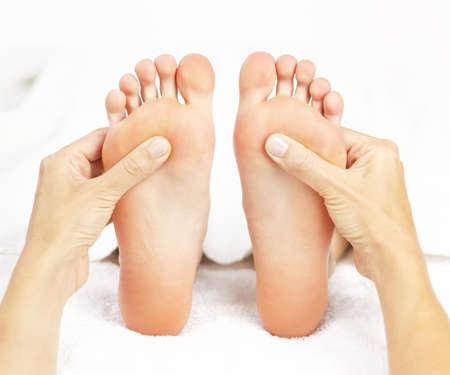 Vrouwelijke handen geven van massage aan zachte blote voeten Stockfoto