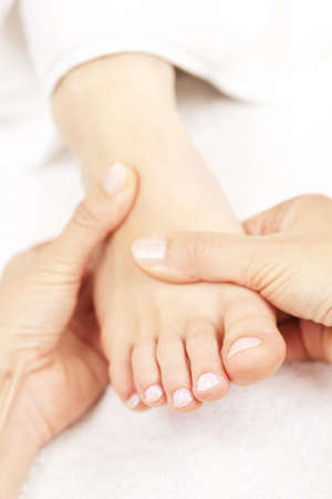 Female hands giving massage to soft bare foot photo