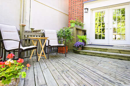 decking: Wooden deck on house with chairs and french doors