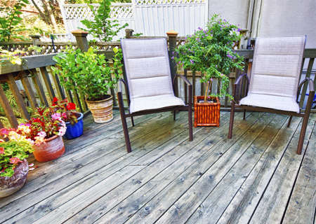 decking: Chairs and plants on wooden deck in backyard of home