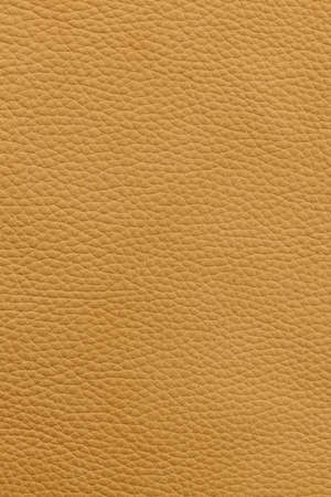Yellow or light brown natural leather background or texture close up photo