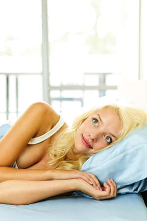 Happy blonde woman laying in bed dreaming and smiling photo
