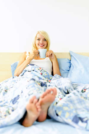 Happy blonde woman drinking coffee and relaxing in bed in the morning