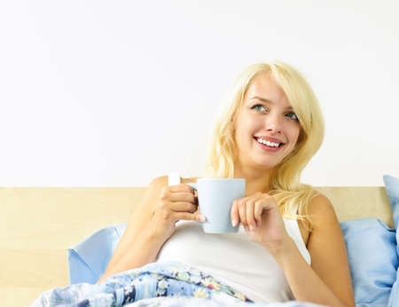 Smiling blonde woman drinking coffee and relaxing in bed in the morning Stock Photo - 10822214